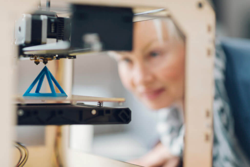 Mature smiling woman working by 3d printer. Selective focus to object in the 3D printer. She is starting printing process for her new 3d project.